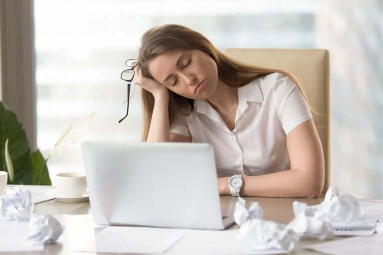 A woman falling asleep at her computer.