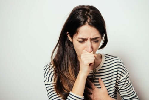 Woman in a striped shirt coughing.