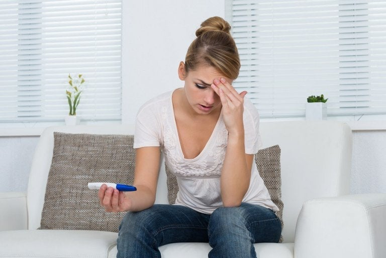 Worried woman after taking a home pregnancy test.