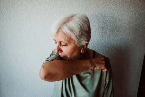 An elderly woman coughing into her arm.