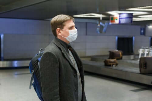 A man using a mask in an airport.
