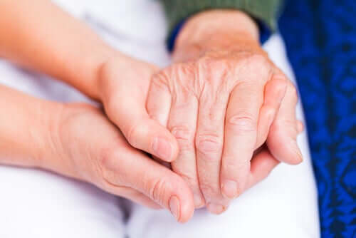 People holding hands, one with the pain of rheumatoid arthritis
