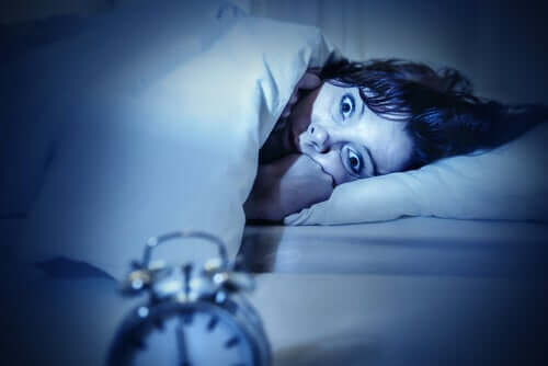 A woman laying awake in bed with sleep paralysis.