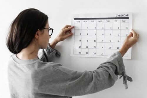 A woman putting a calendar on a wall.