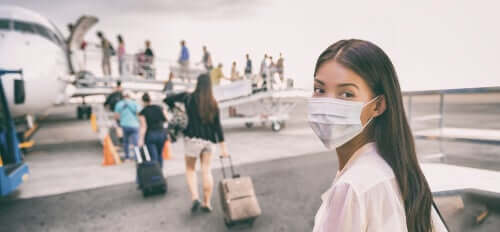 A woman wearing a face mask to go on a plane.