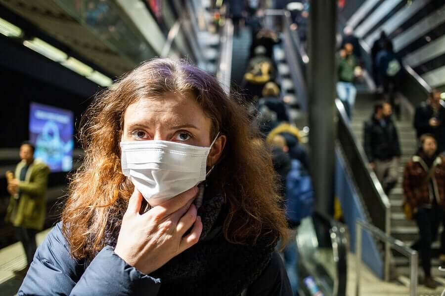 A woman wearing a medical mask.
