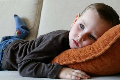 A boy laying on the couch watching television.