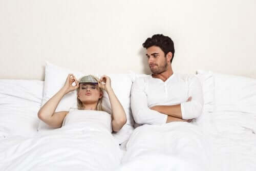 Couple in bed, dealing with sexual frustration.