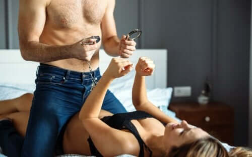 Couple in bed using handcuffs to reactivate their libido.