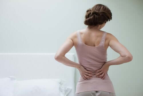 Woman with back pain, one of the symptoms of fibromyalgia.