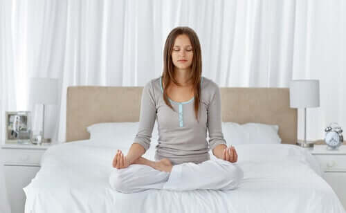 A woman meditating in bed.