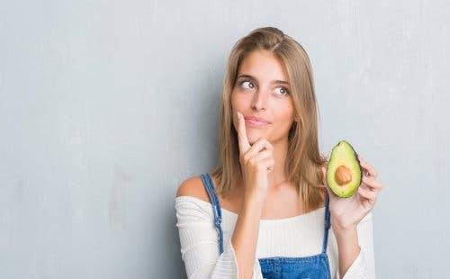 A woman holding an avocado.