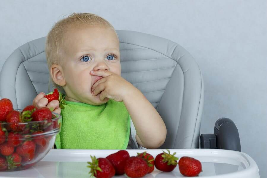 A baby eating strawberries.