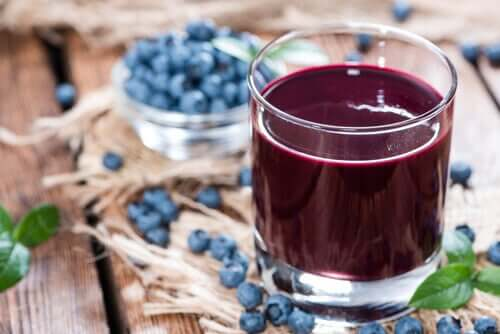 Glass of blueberry sauce with blueberries in the background.