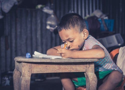 Child writing in notebook.