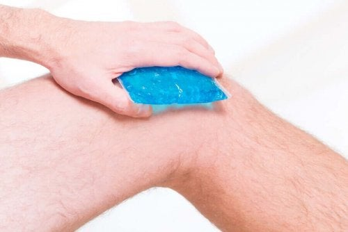 A person putting a cold compress on their knee.