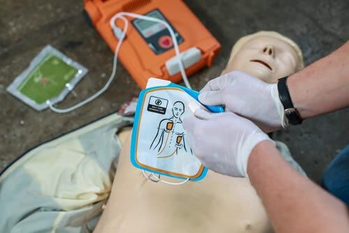 Using defibrillator on practice dummy for cardiopulmonary arrest.
