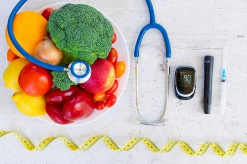 Instruments for diabetes care next to a bowl of fruits and vegetables.