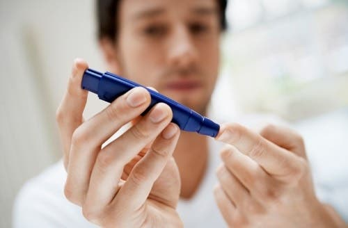 A diabetic man testing blood sugar.