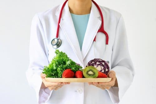 A doctor holding a plate of fruits and vegetables.