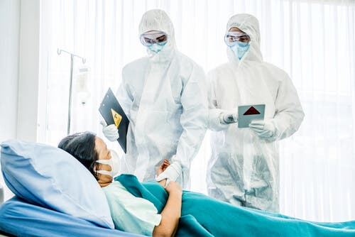 Doctors wearing PPE to see a patient.