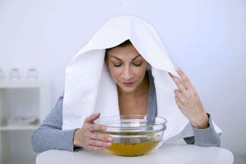 Woman with towel on her head breathing eucalyptus vapors from a bowl.
