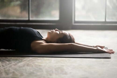 Woman laying on her back on a yoga mat.