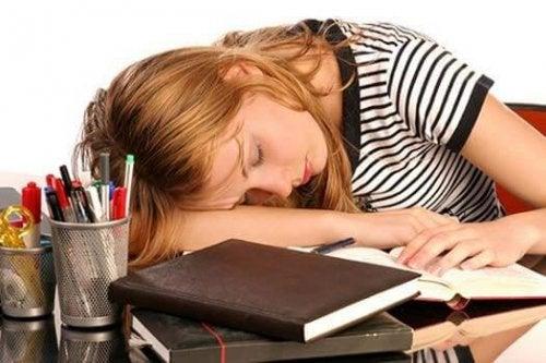 Woman with high ferritin sleeping on desk.