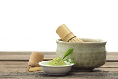 A little bowl of matcha tea powder next to a bigger bowl.