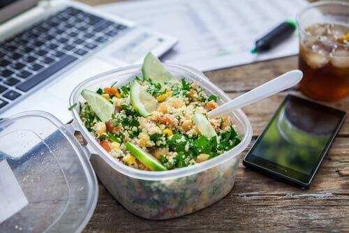 Salad on desk next to phone and laptop.