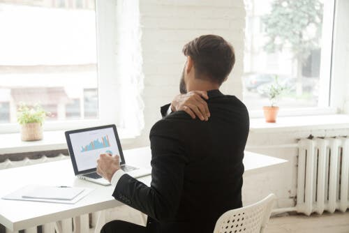 Man in sedentary job, sitting at desk and holding shoulder.