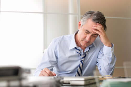Stressed man in office with head in hand.