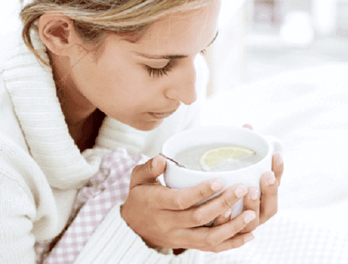 A woman drinking a cup of tea.