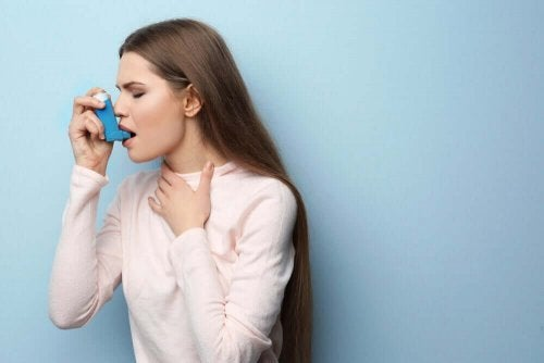 Woman using inhaler.