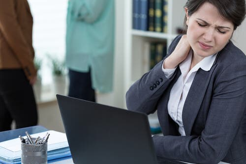 Woman with a sedentary job, sitting in front of a computer with neck pain.