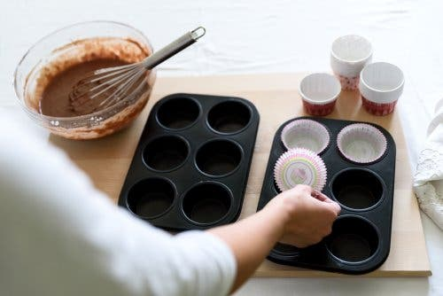 A person making chocolate and orange muffins.