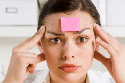 A woman with a sticky note on her forehead.