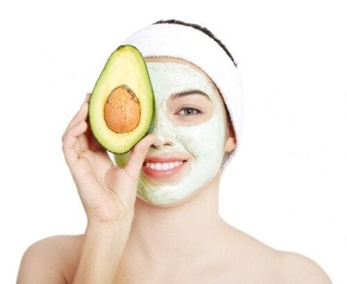 Woman holding an avocado with a mask on to reduce the appearance of wrinkles