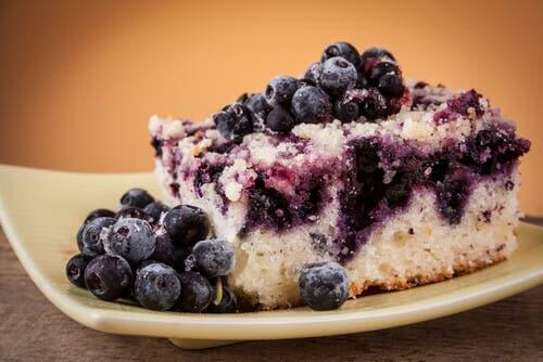 Blueberry cake on a plate with blueberries on top.