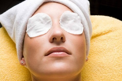 Woman with cold compresses on her eyes.