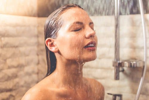 Woman taking a cold shower to relieve varicose veins.