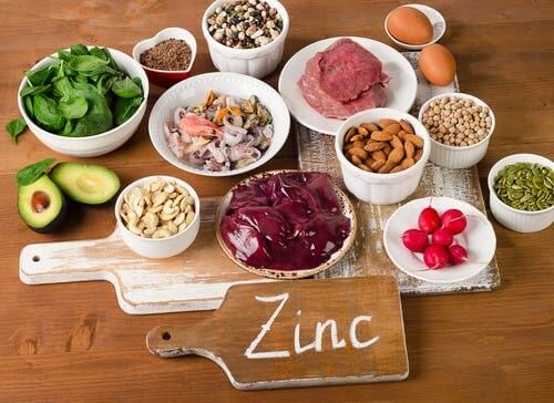 Different foods with zinc to include in your diet with a cutting board.