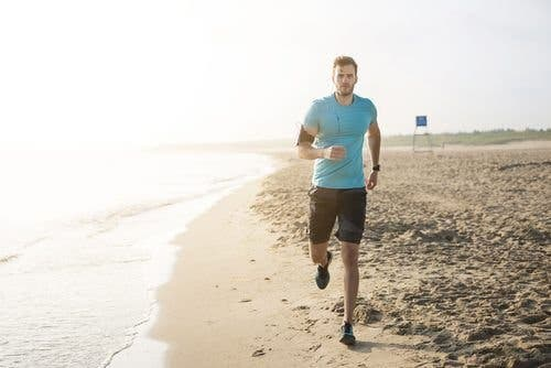 Man running on the beach happy and healthy