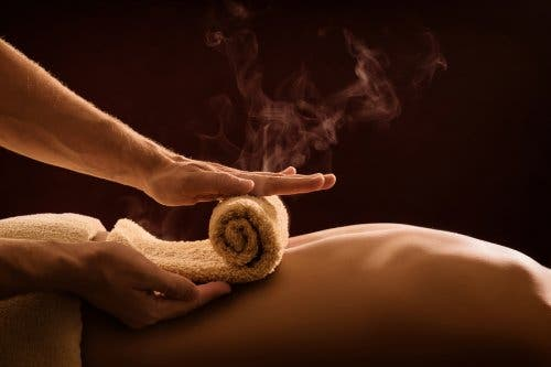 Rolling a hot towel on a person's back.