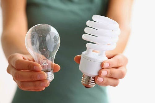 Woman holding up LED light bulb next to old light bulb.