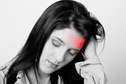 Woman suffering a migraine attack, with forehead highlighted in red.