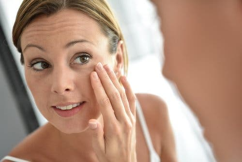 Woman looking at her perfect skin in the mirror reduce the appearance of wrinkles