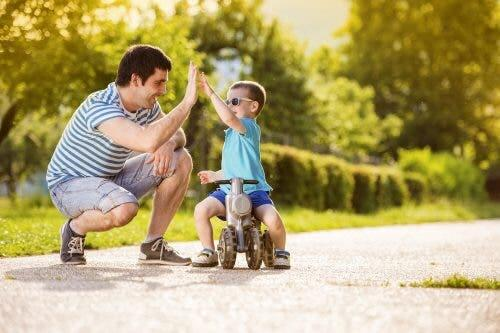 A dad giving his son a high-five to teach resilience and hope