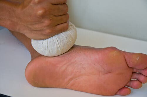 A person applying a cold compress on their foot.