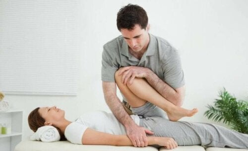 Physical therapist bending woman's leg to treat hip adductor tendinopathy.